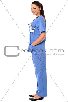 Title:Side pose of a young female doctor in uniform