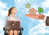 Businessmans hand holding an illustration of house with tree