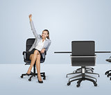 Smiling businesswoman sitting in chair and raising right hand