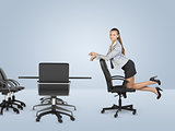 Busineswoman kneeling on chair and looking at camera
