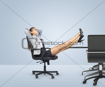 Businesslady sitting in chair with her hands behind head