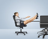 Businesslady sitting profile in chair with her crossed legs on table