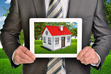 Estate agent showing photo with house on tablet screen