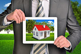 Estate agent showing photo with house on tablet screen holding