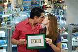 Happy Shop Owners kissing And Showing First Dollar