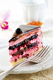 Piece of cake with souffle and blackcurrant jelly on a white pla