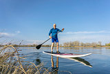Senior male on SUP paddleboard