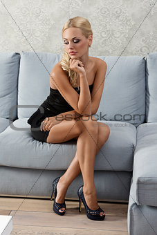 beautiful woman sitting on sofa and looking down