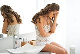 Stressed young woman sitting in bathroom