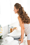 Happy young woman standing in bathroom