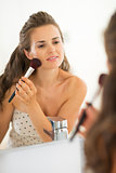 Happy young woman applying makeup in bathroom