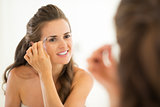 Happy young woman shaping eyebrows in bathroom