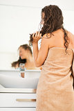 Young woman with wet hair in bathroom. rear view