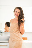 Portrait of smiling young woman with wet hair in bathroom