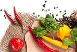 Red and yellow hot chili peppers with salt and fresh basil over white