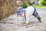 Cute little boy laughing while crawling on stone paved sidewalk