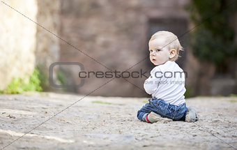Little boy crawling on stone paved sidewalk