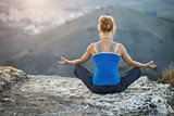 Young woman sitting in asana position and enjoying valley view