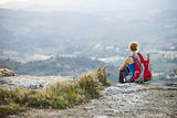 Woman tourist sitting on edge of rock and looking at valley below