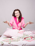 Joyful girl sitting on bed with a bundle of money