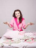 Joyful girl sitting on bed with a bundle of money
