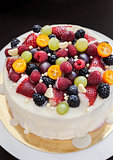 White chocolate cake decorated with fresh berries and fruits