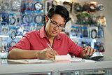 Chinese Man Working In Computer Shop Checking Bills And Taxes