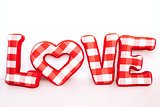 Funny love word of plush red letters on white background. Full plaid textile