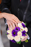 Hands of the groom and the bride on wedding bouquet