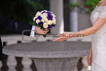 groom gives the bride a bouquet of roses