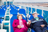 Senior Couple Relaxing On The Deck Of Cruise Ship