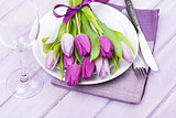 Purple tulip bouquet over plate on wooden table