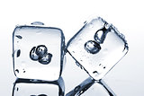 Two melting ice cubes with water dew