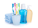 Four colorful toothbrushes, cosmetics bottles and towel