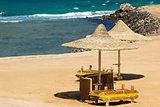Deserted beach with wattled sun umbrellas