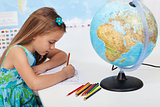 Little girl coloring the world map in geography class