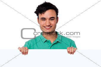 Casual young boy holding blank whiteboard