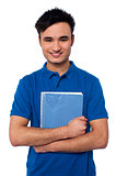 Smiling student embracing his note book
