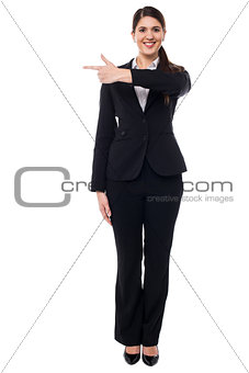 Attractive corporate woman pointing away