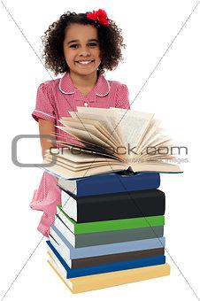 Portrait of pretty schoolgirl reading textbook