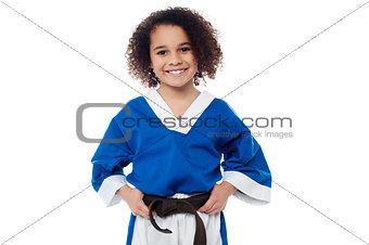 Little girl adjusting her brown karate belt