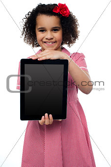 Smiling african american girl presenting tablet pc
