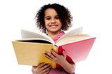 Adorable school girl reading a book with a smile