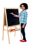 Happy schoolchild writing on blackboard