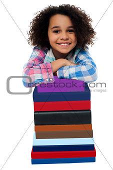Smart little girl leaning over pile of books
