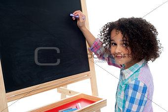 Beautiful little girl writing on classroom board