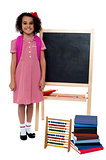 Smiling school girl standing near the blackboard