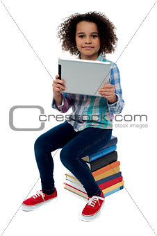 Adorable kid with tablet pc sitting on books