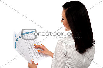 Back pose of businesswoman reading reports