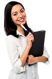 Female executive holding business file and pen